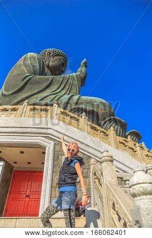 Happy tourist showing the Tian Tan Buddha or Big Buddha at Ngong Ping on Lantau Island, icon of Hong Kong, China. Young woman enjoying travel in Asia. Traveler asia concept.