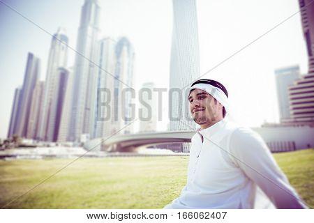young arabian man sitting in the grass at dubai marina, relaxing.