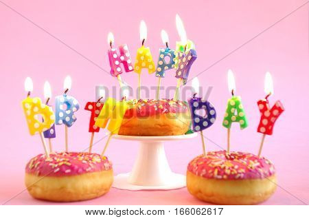 pink donuts as birthday cake with happy birthday candles
