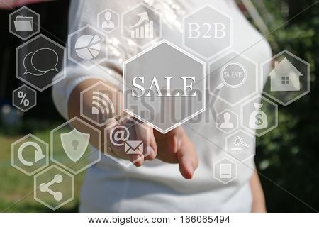 A businesswoman pushes a button SALE on the touch screen the web . The concept of online auctions, shopping, real estate .