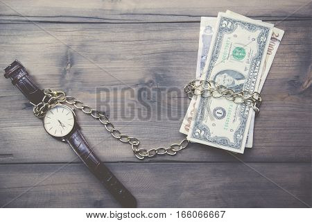 Pocket watch and cash money on wood