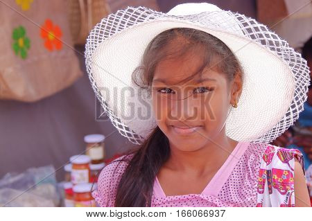 RODRIGUES ISLAND, MAURITIUS - NOVEMBER 10, 2012: Portrait of a pretty girl with a straw hat posing at the market in Port Mathurin