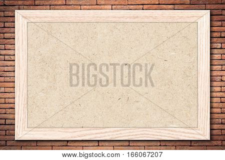 Chipboard or Empty bulletin board with a wooden frame on brick wall background with copy space for text or image.