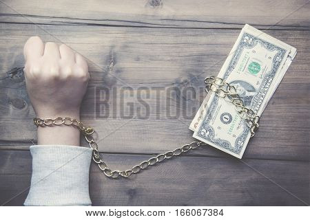 Hand in handcuffs on dollar banknotes table