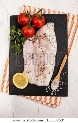 hake fillet with crushed black peppercorn wet tomato lemon slice and parsley