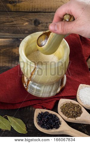 man prevents the spices in a mortar on a wooden background