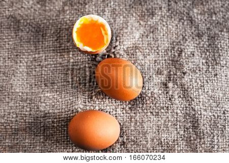 Hard boiled eggs with orange yolk in rustic style  on wooden background close up