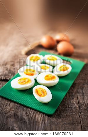 Hard boiled eggs sliced in halves on cutting board wooden background close up