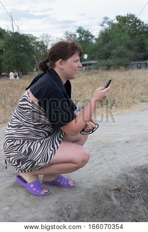Keep cell phone woman squatting and communicate