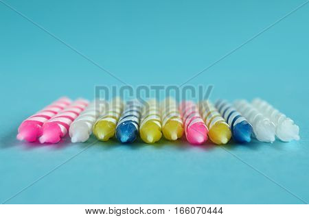 colorful birthday candles in front of a blue background
