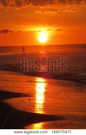 Orange sunrise at beach, surf, reflection  on sand and human silhouette in distance