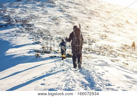 tourists hikers traveling on the snowy mountains to the top at sunset the concept of the path to purpose and success