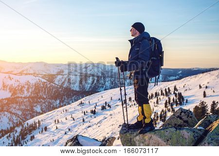 man tourist hikers standing on snowy mountain on the way to the top at sunset the concept of the path to purpose and success