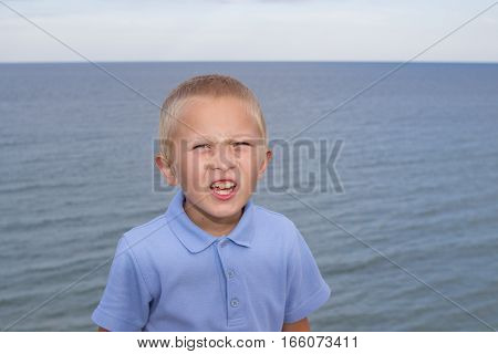 boy with emotions with open mouth on a background of the sea