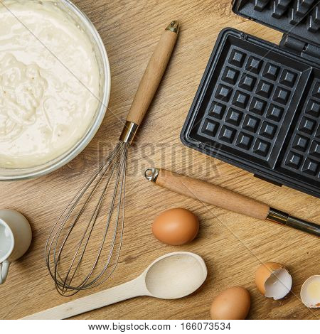 Making waffles at home - waffle iron, batter in bowl and eggs. Cooking background.