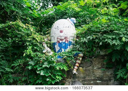 Decaying Plaster egg with arms, legs, face, top hat, bowtie and striped socks sitting on stone wall covered in plants.