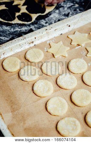 Shaped cookies waiting for being baked on a baking pan.