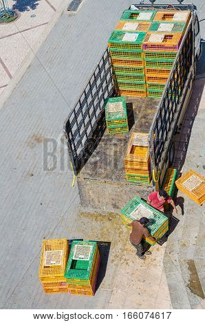 Aerial view of two Moroccan men unloading colorful animal boxes from truck, Chefchaouen, Morocco, North Africa.