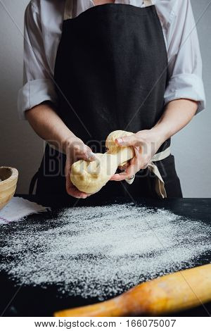 Person preparing to beat up a dough on a table covered with flour.