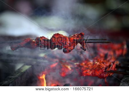 Delicious tandoori chicken on a barbecue covered with Indian delicious spices