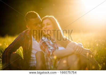 Multi racial couple dating in nature - sitting in grass at sunset