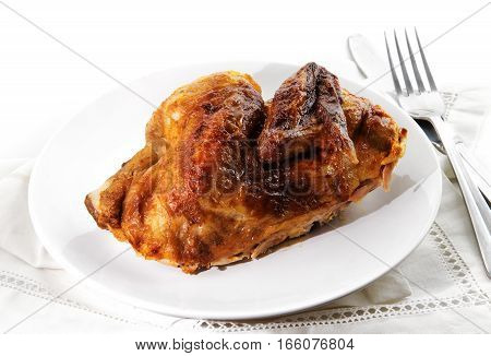 grilled half chicken served on a plate napkin and silverware background fades to white selected focus narrow depth of field