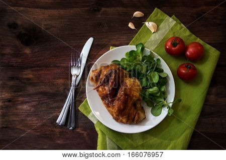 grilled half chicken with tomatoes corn salad and garlic white plate green napkin and silverware on a dark rustic wooden table with copy space