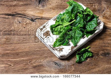 Fresh green spinach leaves on rustic kitchen board. Healthy organic food concept