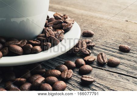 Coffee cup full of coffee beans on the wooden table. Horizonral