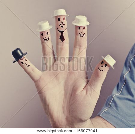 Hand painted on fingers funny faces and little hats