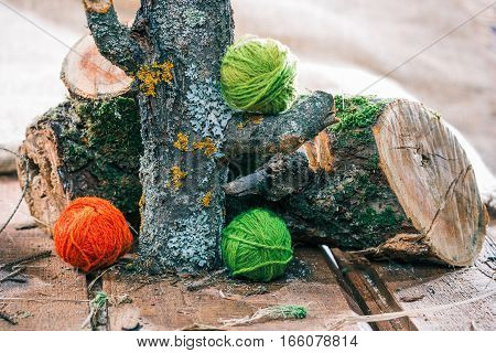 Red and green wool clews on natural raw logs