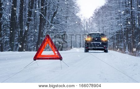 Broken up car and warning triangle on the snowy winter road