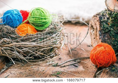 Colorful yarn balls in bird nest on rough wood boards