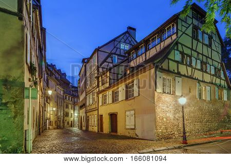 Street with historical houses in Colmar city center Alsace France. Evening