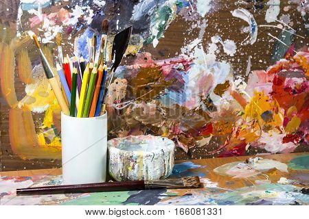 The palette of artist with a Cup for mixing paints and a brush and pencils and a knife