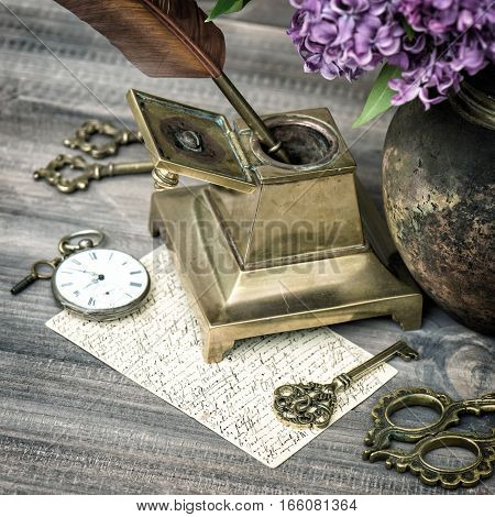 Antique office accessories with lilac flowers. Retro style toned photo selective focus.