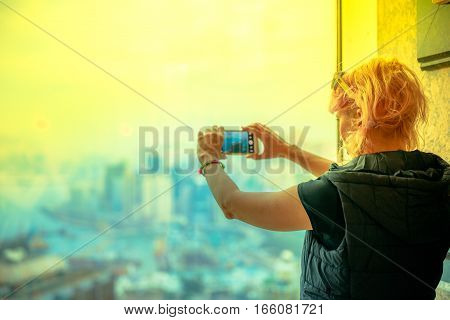 Scenic view of Hong Kong skyline at sunset. Observation deck with defocused background. Young tourist taking picture with smartphone enjoying view over Victoria Harbour.Travel and tourism asia concept