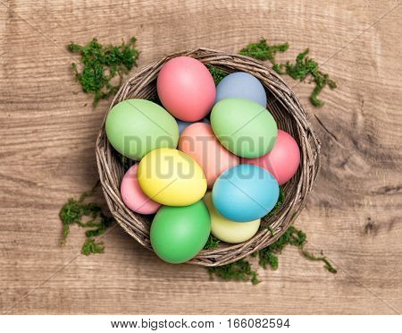 Easter eggs in basket on wooden background. Top view