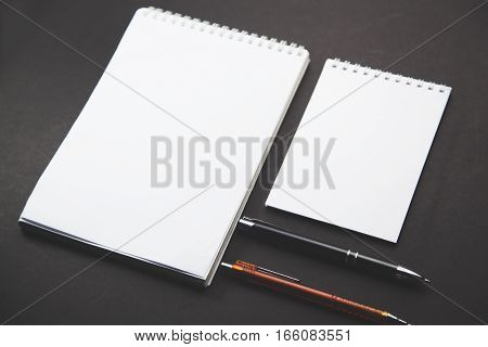 two Notebook with two pen on wooden table