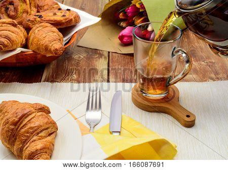 tea with croissants, tea in a glass cup, croissant, tulips, bake, pouring, cup, fork, knife, plate