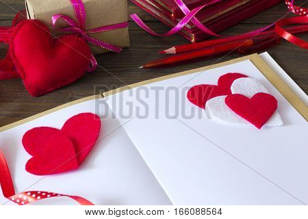 notebook with pen and pencil, the heart of felt and gift ribbons in the background on the table