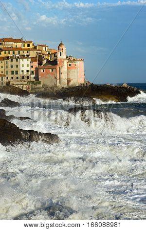 Tellaro village with the Church of St. George (San Giorgio) with cliffs and rough sea. La Spezia Liguria Italy