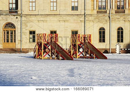Two wooden red and yellow children's slides built on the square in front of the palace in winter