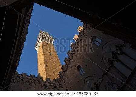 Torre del Mangia 87 m. bottom view (Tower of Mangia) on blue sky with clouds. Siena Toscana (Tuscany) Italy