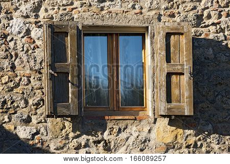 Typical old window with wooden shutters in Tuscany (Toscana) Italy Europe