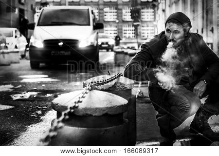 Man smokes an electronic cigarette on the streets of a big city. Vaping. Black and white photo.