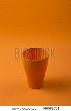 Still-life with a glass of orange on an orange background