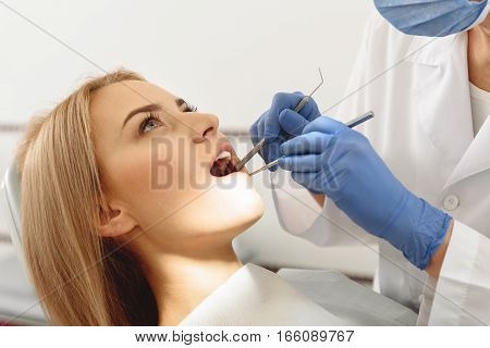 Odontologist taking care of set of cavities with dental explorer and mirror. Thoughtful woman leaning with wide opened mouth while looking at ceiling