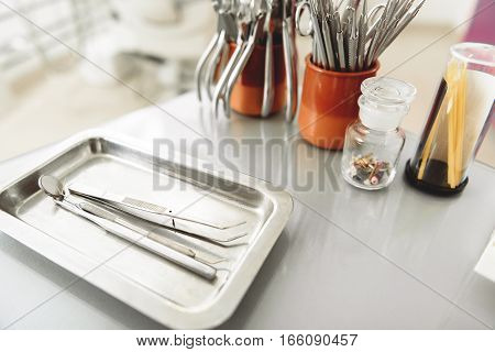 Dental explorer with mirror, bistoury, scisors, cleaning stick and other instruments being on a surface of table in apartment of stomatologist