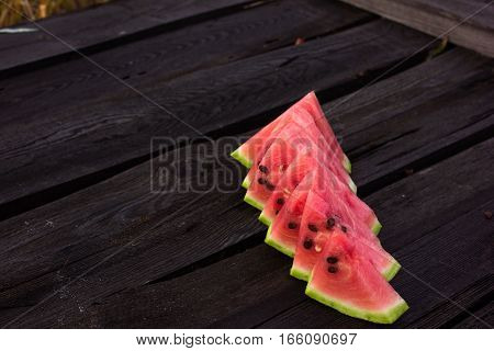 Watermelon slice popsicles on a rustic wood background Popular summer fruit with yummy watermelon